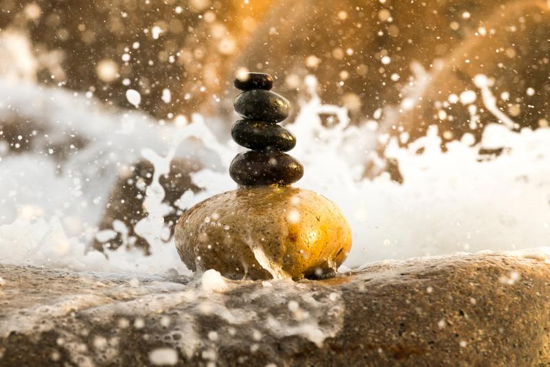 Steine Balancieren zwischen spritzendem Wasser